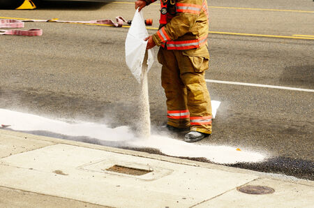 Fire fighers spreading absorbant at a four vehicle accident involving two large trucks resulted in a single injury and a diesel fuel spill. July 17, 2012 in Roseburg Oregon Stock Photo - 35104872