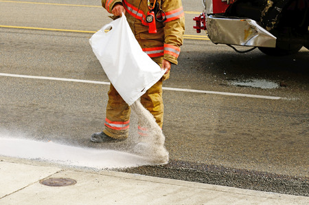 Fire fighers spreading absorbant at a four vehicle accident involving two large trucks resulted in a single injury and a diesel fuel spill. July 17, 2012 in Roseburg Oregon photo