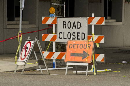 Road closed and detour signs at a downtown urban construction site