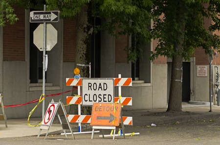 detour: Road closed and detour signs at a downtown urban construction site