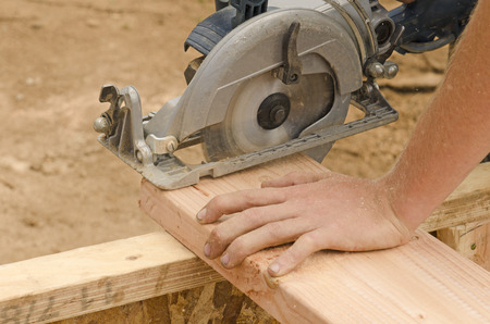 contractor: Framing contractor using a circular hand  saw to trim wood studs to length. Stock Photo