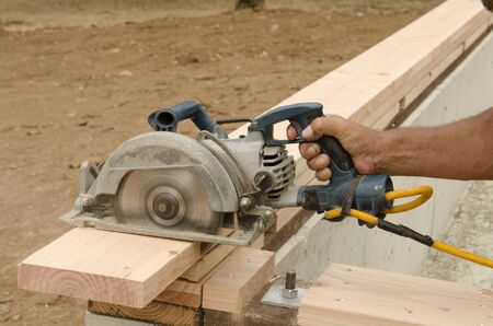 stud: Using a power circular saw to trim the top plate board of a stud lumber wall  on a new luxury custom home Stock Photo