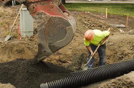 掘削建設請負業者国内黒プラスチック下水道をインストールするドレインの砂利充填新しい商店街 写真素材