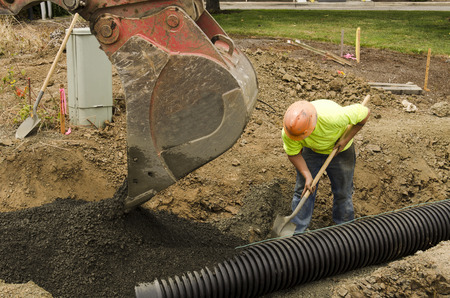 Excavation construction contractor installing a domestic black plastic sewer drain on a new commercial street filling with gravel Stock Photo