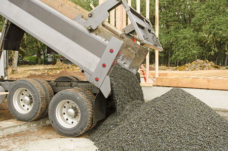 Excavation contractor delivering a load of fill gravel for a garage at a luxury custom home project Reklamní fotografie