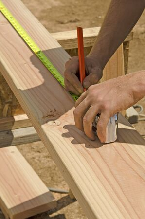 stud: Building construction contractor carpenter measuring a wood wall stud with a tape measure