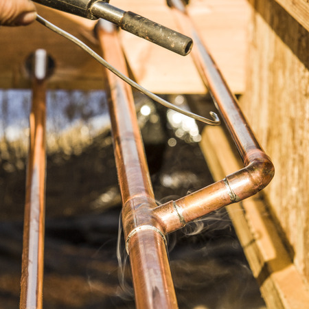 Plumbing contractor works sweating the joints on the copper pipe domestic water system on a luxury custom home Standard-Bild
