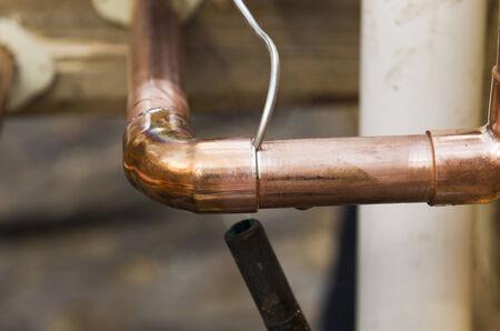 ca�er�as: Contratista de plomer�a trabaja sudando las articulaciones en la instalaci�n de la casa tubo de cobre en una casa de dise�o de lujo