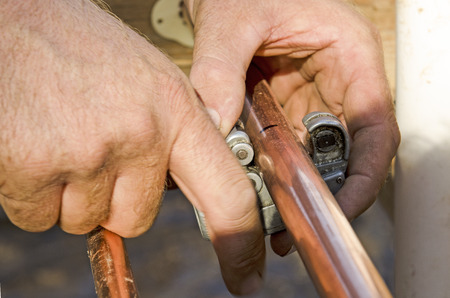 custom home: Plumbing contractor works cutting copper pipe domestic water system on a luxury custom home