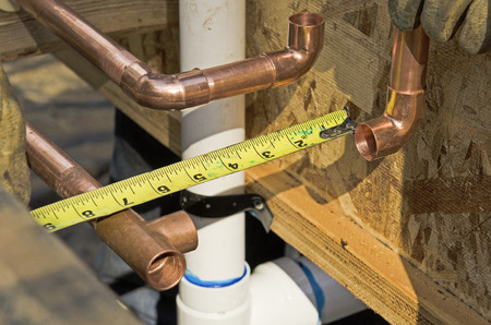 Plumbing contractor works on the copper pipe domestic water system on a luxury custom home