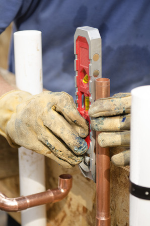 custom home: Plumbing contractor works on the copper pipe domestic water system on a luxury custom home
