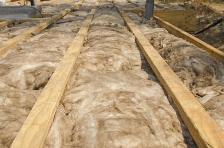 Fiber glass insulation batts unfaced between wood flooring joist cavities of a custom luxury under construction