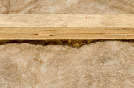 housebuilding: Fiber glass insulation batts unfaced between wood flooring joist cavities of a custom luxury under construction