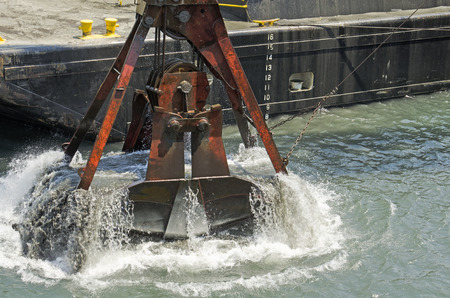 A cable powered crane uses a clam shell bucket to remove sand in a dredging operation in Port Orford Oregon