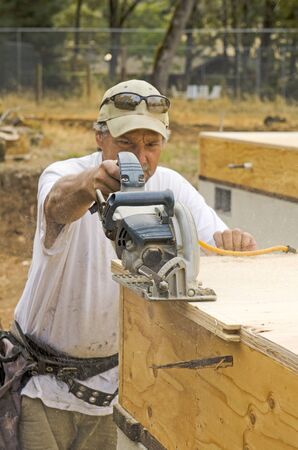 framer: Framing contractor uses a circular had saw to cut and trim plywood sub floor panels on a new luxury custom residence Stock Photo