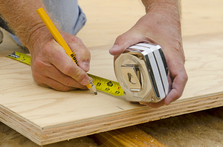 joist: Framing contractor uses a tape measure to trim plywood sub floor panels on a new luxury custom residence Stock Photo
