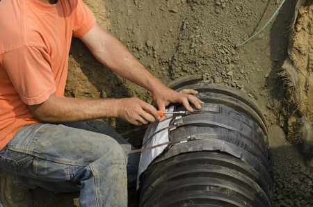 gasket: Excavation contractor uses a field repair coupler tape gasket to install a tee in plastic drain pipe for a new commercial street storm drain sewer
