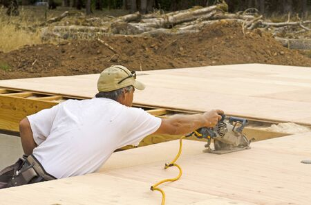 framing: Framing contractor uses a circular had saw to cut and trim plywood sub floor panels on a new luxury custom residence Stock Photo