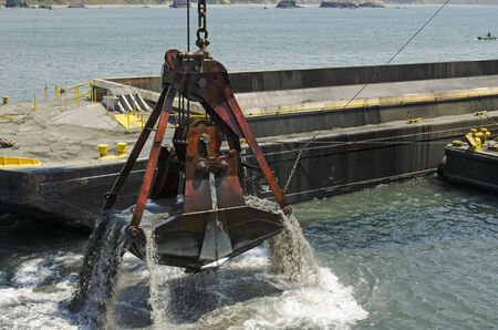 dredging: A cable powered crane uses a clam shell bucket to remove sand in a dredging operation in Port Orford Oregon Stock Photo
