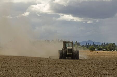 Large agricultural tractor pulling a steel disc harrow to prep the soil for planting with fall storm approaching Stok Fotoğraf - 36944601