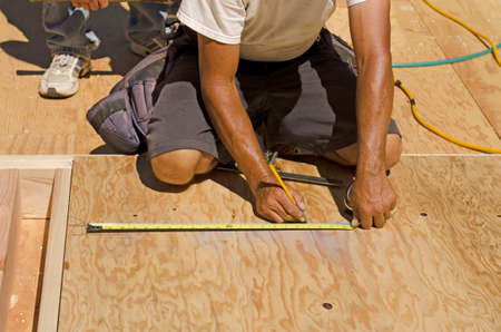 stud: Framing Contractor cutting in a window or door opening in outside bearing wood stud wall Stock Photo