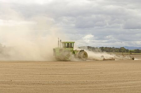 Large agricultural tractor pulling a steel disc harrow to prep the soil for planting with fall storm approaching Stok Fotoğraf - 36944710