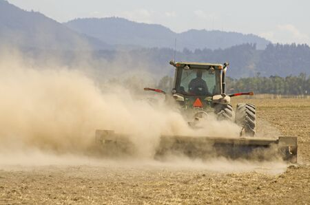 A large tractor doing soil prep using a chisel flow harrow before planting