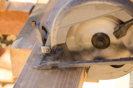 cut off saw: Building contractor worker using hand held worm drive circular saw to cut boards on a new home construction project