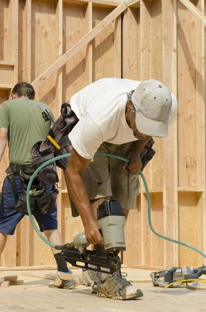 custom home: Framing construction contractor installing sub siding on a wood frame wall of a new luxury custom home