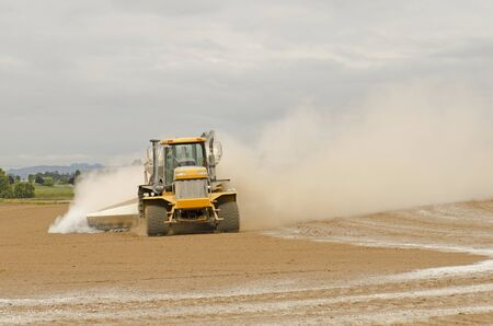 Agricultural lime being spread by a big tired truck or tractor  on a newly plowedb farm field Imagens