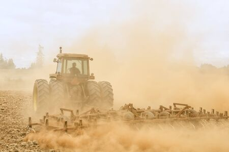 PrEP: A large tractor doing soil prep using a chisel flow harrow before planting