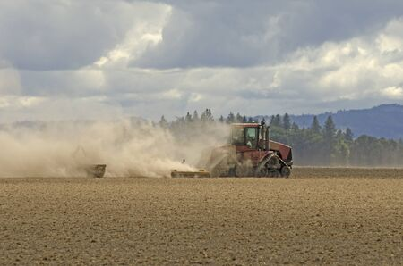 Large agricultural tractor pulling a steel disc harrow to prep the soil for planting with fall storm approaching