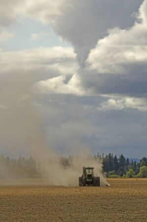 PrEP: Large agricultural tractor pulling a steel disc harrow to prep the soil for planting with fall storm approaching