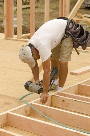 framer: Framing building contractor framing up a wall section for a luxury custom house