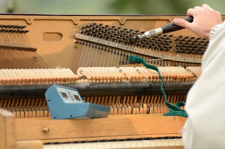 A piano tuner working on an old upright just before a fair concert