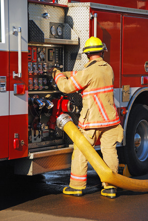 Firefighters setting up supply lines at a heavy streams fire training