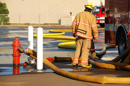 turnouts: Firefighters setting up supply lines at a heavy streams fire training