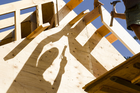 Construction framing contractor carpenter building out the gabel end of the roof with purlin and facia trim boards