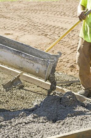 curb: Concrete construction contractor installing a sidewalk, curb and storm drainage gutter on a new urban road street project Stock Photo