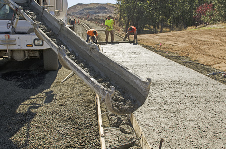 Concrete construction contractor installing a sidewalk, curb and storm drainage gutter on a new urban road street project Imagens