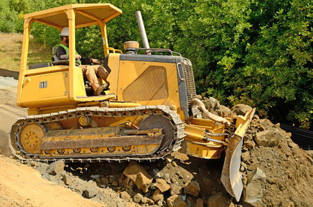 Roseburg Oregon, USA - August 11, 2012 - A small bulldozer moves and levels rock and dirt on a new road constuction project