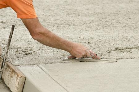 Concreet contractant het installeren van een dilatatievoeg in een stoep, stoeprand en storm drainage goot op een nieuw stedelijk straat project Stockfoto