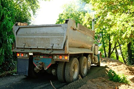 river side: A dump truck unloading gravel for a river side walking path in a small park city park in Oregon
