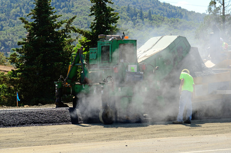 asphalt paving: A paving crew  putting down a layer of asphalt on a new highway intersection project Stock Photo