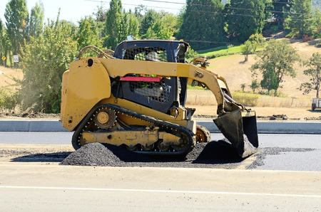 compact track loader: A paving crew  putting down a layer of asphalt on a new highway intersection project Stock Photo