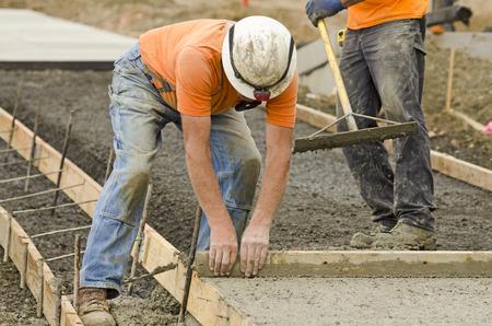 Concreet contractant het installeren van een stoep, stoeprand en storm drainage goot op een nieuw stedelijk straat project Stockfoto