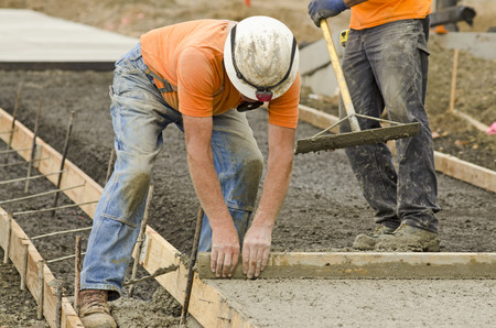 Concrete construction contractor installing a sidewalk, curb and storm drainage gutter on a new urban road street project Stock Photo