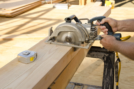 custom home: Framing construction contractor cutting a beam for a window header on a wood frame wall of a new luxury custom home Stock Photo