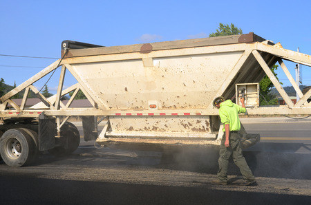 A large belly dump truck delivers fresh asphalt for a paving project of a new road and intersection project