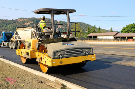 compacting: Drum tandem vibratory rollers compacting down a fresh layer of paving on a new road interchange project Stock Photo